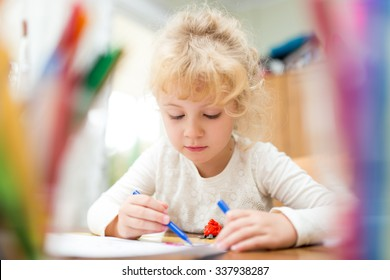 Portrait of child girl drawing at home