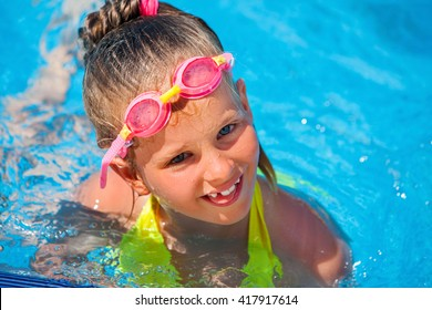 Portrait of child girl wearing googles on water slide at aquapark . Summer water holiday reacriation . Outdoor.