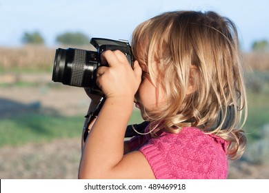Portrait of a child holding a photo camera