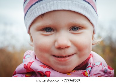 Portrait of a child of a little girl in a warm hat and warm clothes in an autumn day