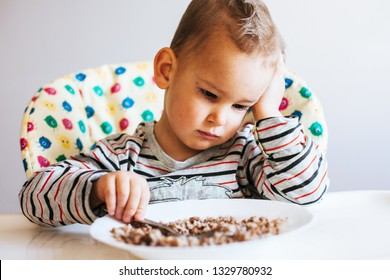 Portrait of child with no appetite in front of the meal