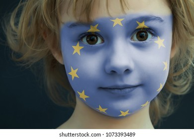 Portrait of a child with a painted flag of Europe on her face, closeup.