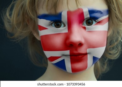 Portrait of a child with a painted flag of the Great Britain on her face, closeup.