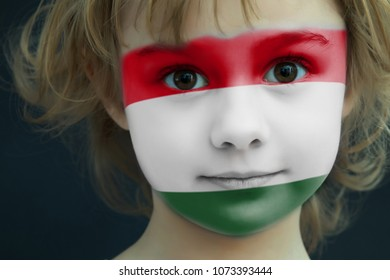 Portrait of a child with a painted flag of Hungary on her face, closeup.