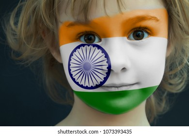 Portrait of a child with a painted flag of India on her face, closeup.
