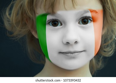 Portrait of a child with a painted flag of ireland on her face, closeup.
