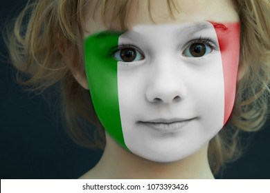 Portrait of a child with a painted flag of Italy on her face, closeup.