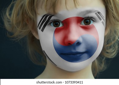 Portrait of a child with a painted flag of south korea on her face, closeup.