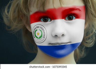 Portrait of a child with a painted Paraguay flag on her face, closeup.