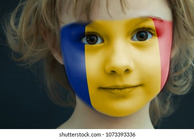 Portrait of a child with a painted Romanian flag on her face, closeup.