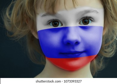 Portrait of a child with a painted Russian flag on her face, closeup.