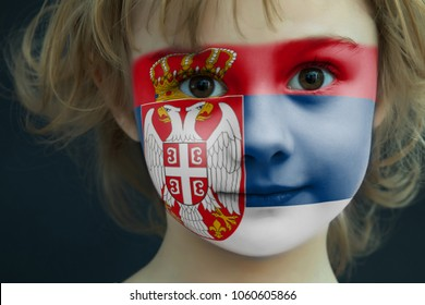 Portrait of a child with a painted Serbian flag on her face, closeup.