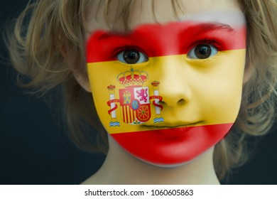 Portrait of a child with a painted Spanish flag on her face, closeup.