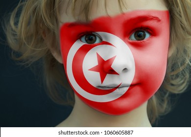 Portrait of a child with a painted Tunisian flag on her face, closeup.