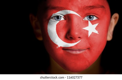 Portrait of a child with a painted  turkish flag, closeup