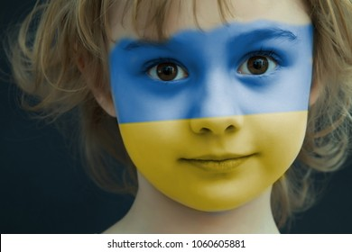 Portrait of a child with a painted Ukrainian flag on her face, closeup.
