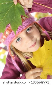 Portrait of child photographed with autumn leaves close-up. Studio photography on white background