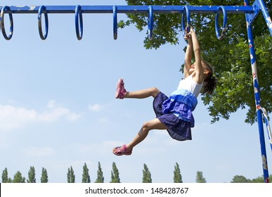 Portrait of a Child Playing and swinging along on Monkey Bars outdoors