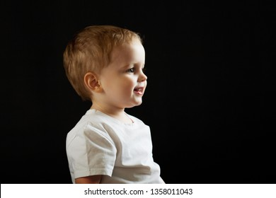 Portrait of a child in profile on a black background. Boy looking forward, concept, copy space right