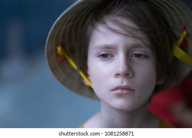Portrait of a child with a sad face in a traditional Vietnamese straw hat