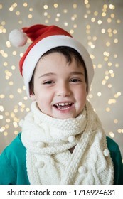 Portrait of child in santa hat, white scarf. New Year, Christmas, winter concept. Lights in the background. Emotional kid face. Cute, funny person. Festive mood. Smiles. Eye contact. Selective focus.