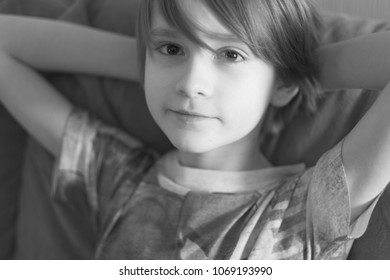Portrait of a child of a schoolboy sitting on a sofa with hands laid behind his head