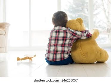 Portrait d'enfant assis dans le salon avec un ours en peluche