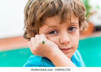 Portrait of a child with a small iridescent green beetle in his hand. Concept of childhood and nature.