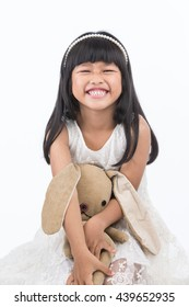 Portrait of a child smiling cuddling with a stuffed toy on white background