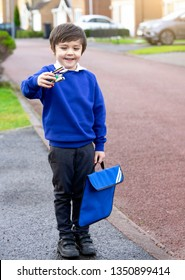 Portrait of Child with smiling face showing toy and carrying bag waiting for schoolbus, Pupil of primary school get ready to studying, Student back to school in first day, Elementary student.