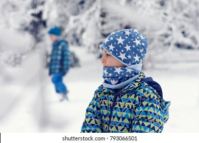 Portrait of a child in snow winter park or forest, profile view, another child in the background.