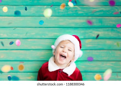 Portrait of child wearing Santa Claus costume. Kid having fun at Christmas time. Merry Xmas concept