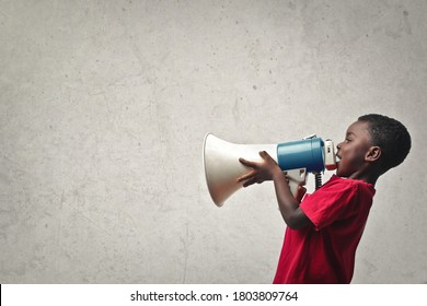 portrait of child yelling into a megaphone