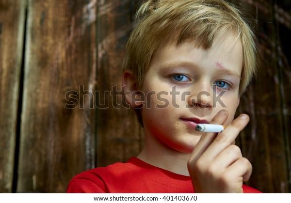 Retrato de niño escolar fumando el Cigarrillo en el patio trasero. Adolescente fuma secretamente el Cigarrillo, fondo de pared de madera, retrato