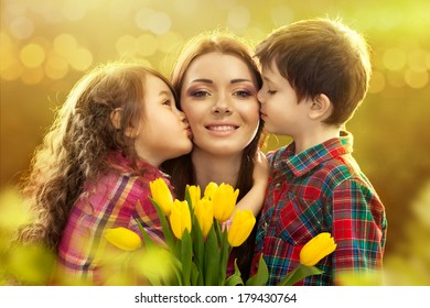 Portrait of children kissing her mother with flowers. Spring, March 8, International Womens, Mothers day, family holiday