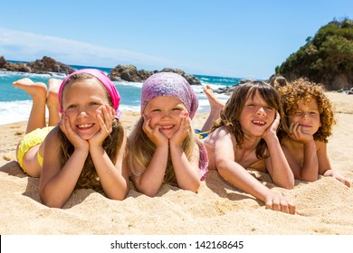 Portrait of children laying on sand at beach.