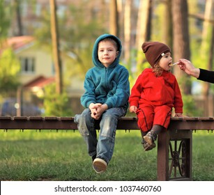 Portrait of children on bench in the spring park, lunch out