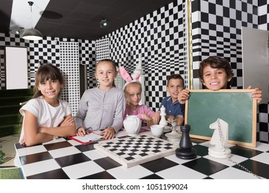Portrait of children playing in the quest room in chess style