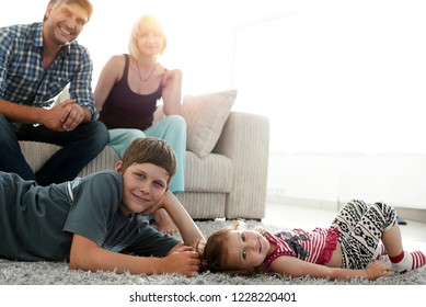 Portrait of children while parents sitting at sofa in living roo