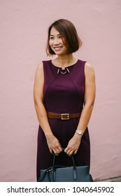 Portrait of a Chinese Asian businesswoman against a pink wall in the day. She is dressing professionally in a dress and is smiling confidently.