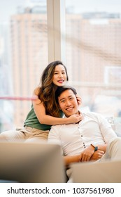 Portrait of a Chinese Asian (Singaporean) couple sitting against the window with the Singapore city in the background. They are in a comfortable apartment and smiling as they hug.