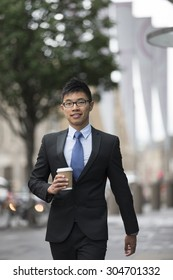 Portrait of a Chinese businessman outside modern office building. Asian businessman smiling & looking at the camera.