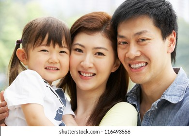 Portrait Of Chinese Family With Daughter In Park