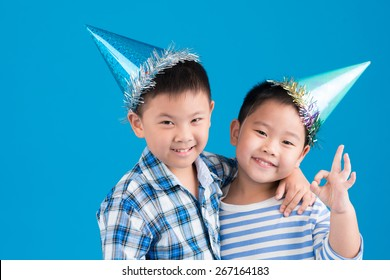 Portrait of Chinese little brothers wearing birthday hats
