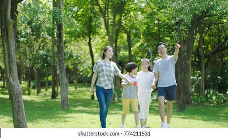 portrait of Chinese parents & kids walking outdoors & laughing