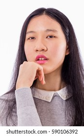 Portrait of Chinese teenage girl looking at camera with chin on hand, serious expression