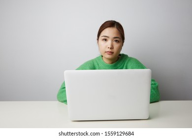 Portrait of Chinese woman posing on the white background and working with her notebook. Isolated.
