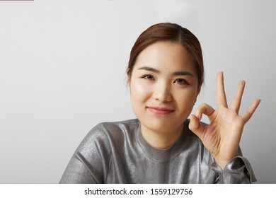 Portrait of Chinese woman posing on the white background with her hand making OK sign. Isolated.