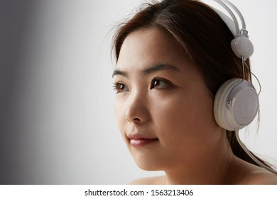 Portrait of Chinese woman posing on the white background with big earphones. Isolated.