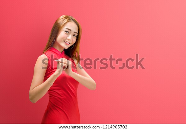 Portrait of chinese woman in traditional dress with congratulation gesture. Happy Chinese New Year